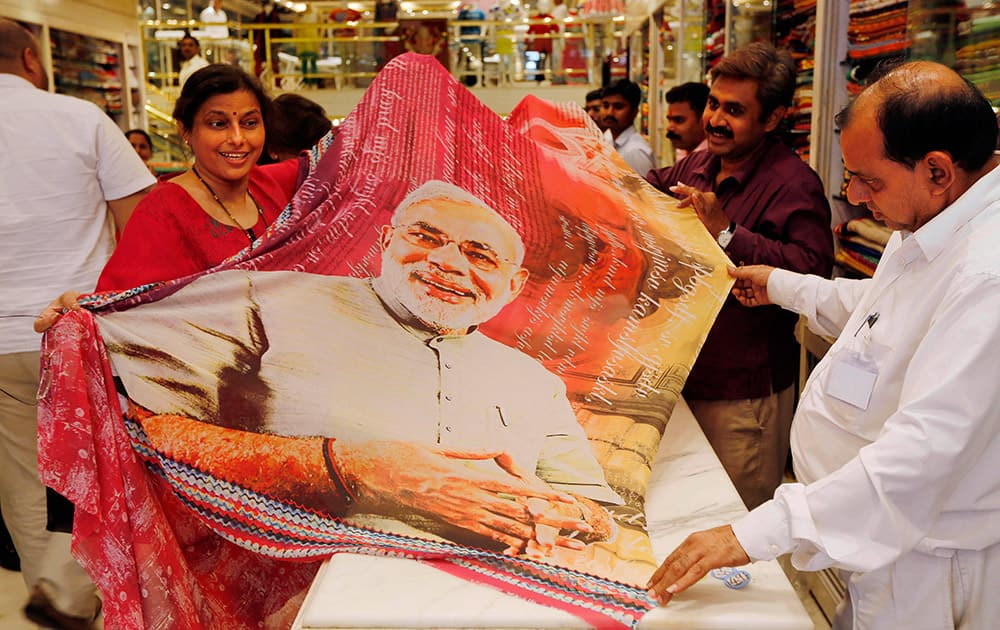 A woman customer holds a sari printed with a portrait of Bharatiya Janata Party`s prime ministerial candidate Narendra Modi at a garments shop in Mumbai.