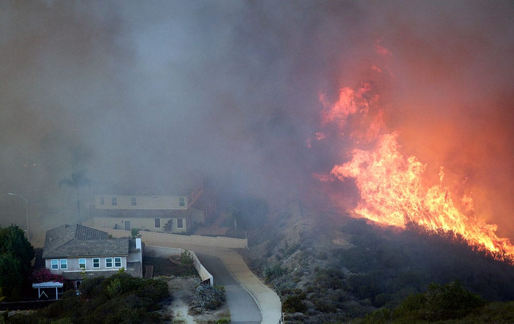 A wildfire approaches homes, in San Marcos, Calif.