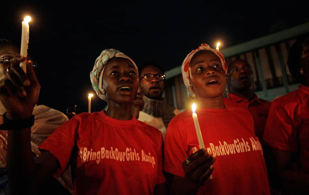 People hold candle light during a vigil to mark one month after the girls of government secondary school Chibok were kidnapped, in Abuja, Nigeria.