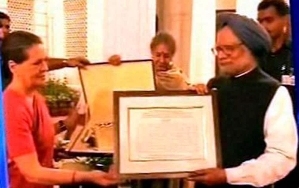 Congress President Sonia Gandhi presents a memento to Prime Minister Manmohan Singh during the farewell dinner hosted by Congress President at her residence 10 Janpath in New Delhi.