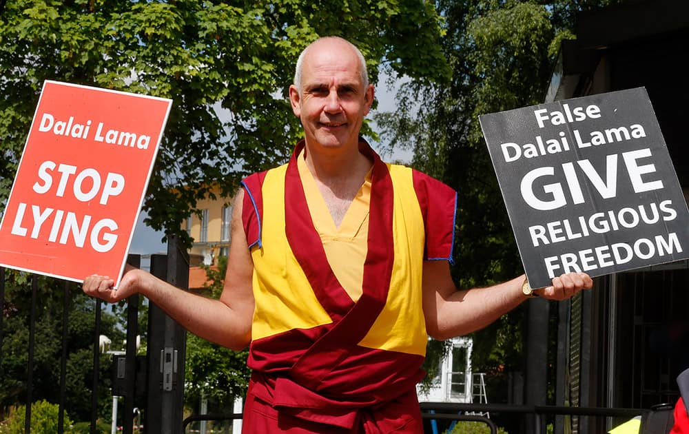 A man holds signs protesting against the Dalai Lama in Frankfurt, Germany. Around hundred western Buddhists and Tibetans called on the Dalai Lama to end discrimination and allow freedom of religion.