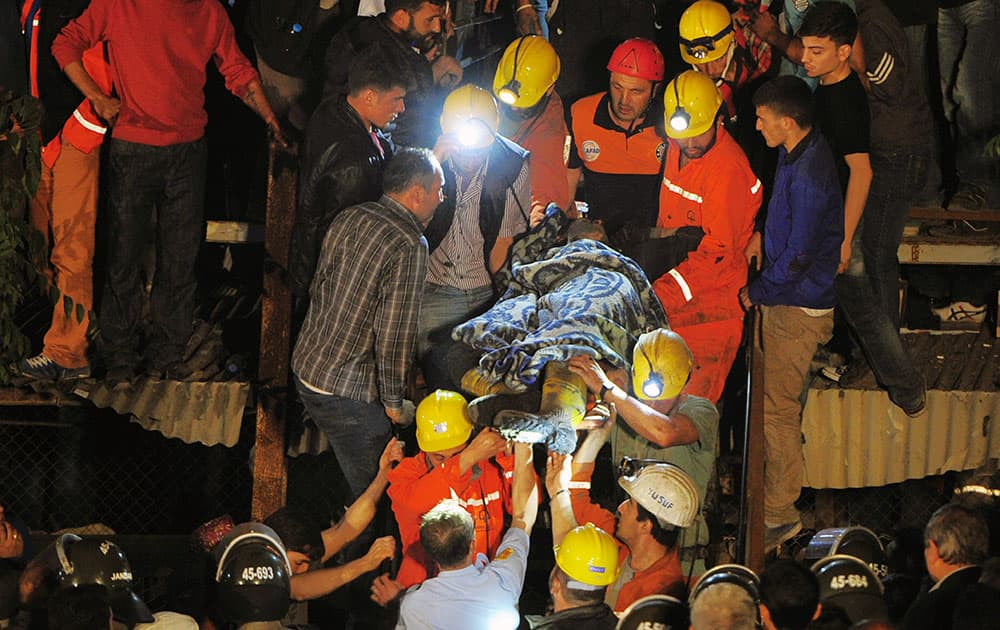 Miners carry a rescued friend hours after an explosion and fire at a coal mine killed at least 17 miners and left up to 300 workers trapped underground, in Soma, in western Turkey.