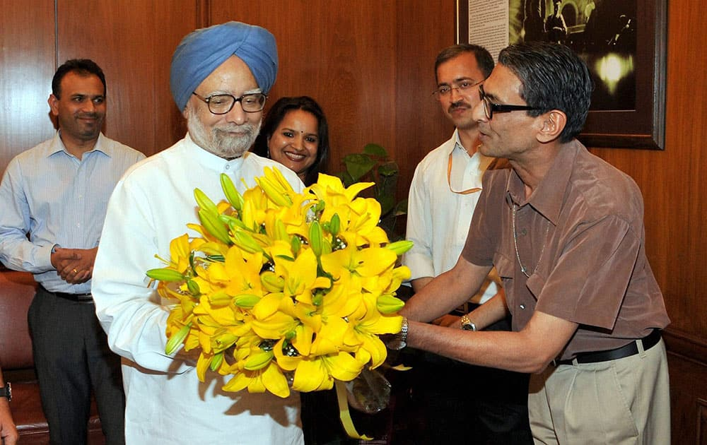 Principal Secretary Pulok Chatterjee presenting a bouquet to Prime Minister Manmohan Sngh who bid farewell to the staff at the PMO in New Delhi.