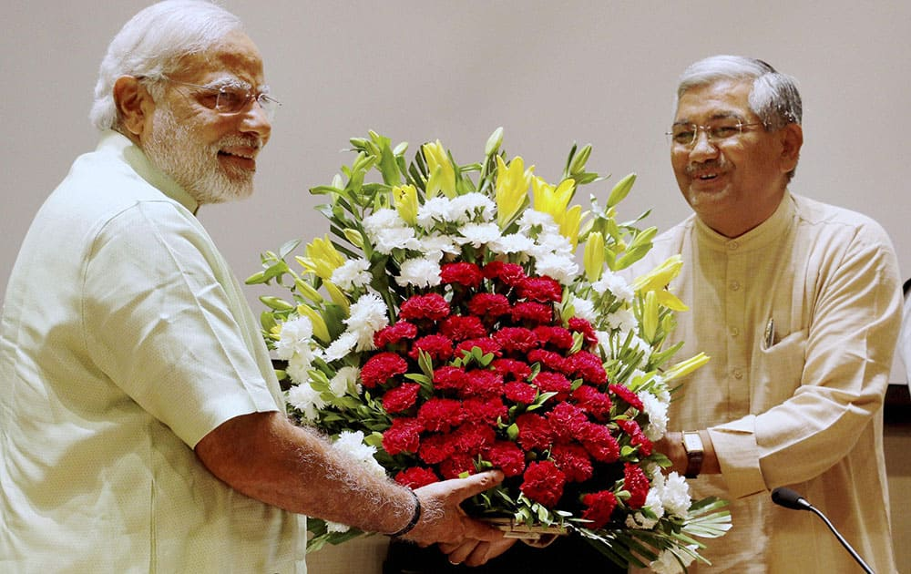 GUJARAT CHIEF MINISTER AND BJP`S PM CANDIDATE NARENDRA MODI IS PRESENTED WITH A BOUQUET BY THE PARTY`S STATE UNIT CHIEF RC FALDU AT A MEETING OF PARTY MLAS IN GANDHINAGAR.