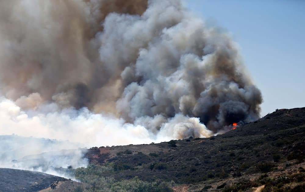 Billowing smoke rises from flames as firefighters begin the trek up the hills to battle a wild fire, in San Diego.