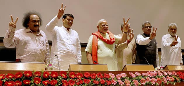 Gujarat Chief Minister and BJP`s PM candidate Narendra Modi flashes victory sign at a meeting with party MLAs in Gandhinagar.