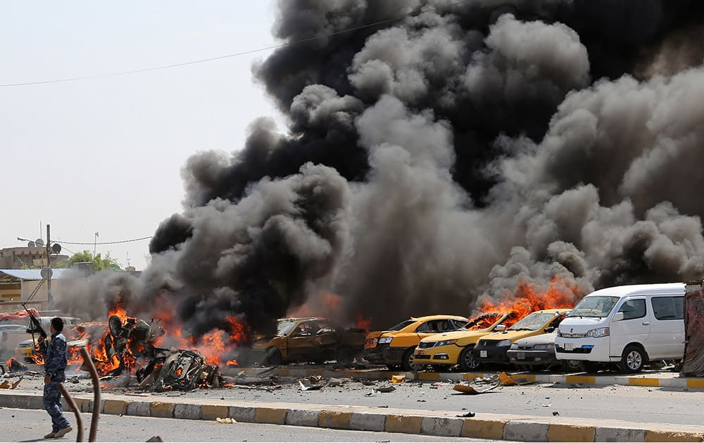 An Iraqi policeman stands near burning vehicles moments after one in a series of bombs hit the Shiite stronghold of Sadr City, in Baghdad, Iraq.