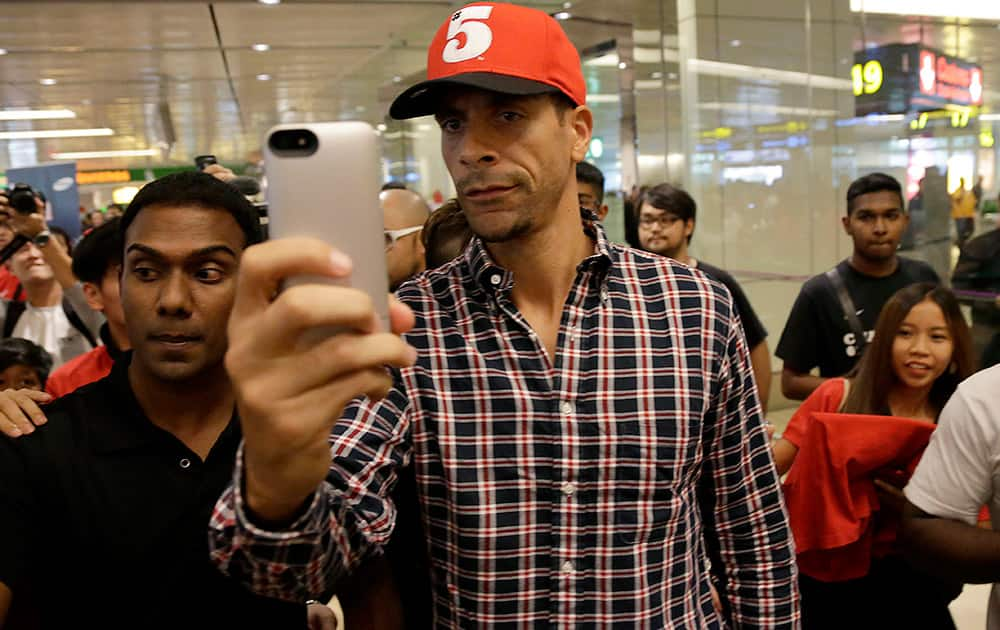 Manchester United`s Rio Ferdinand takes a `selfie` upon arrival at the Changi International Airport in Singapore.
