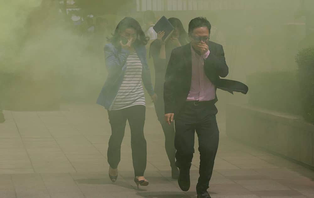 South Koreans cover their faces while escaping from smoke during an emergency fire drill in Seoul.