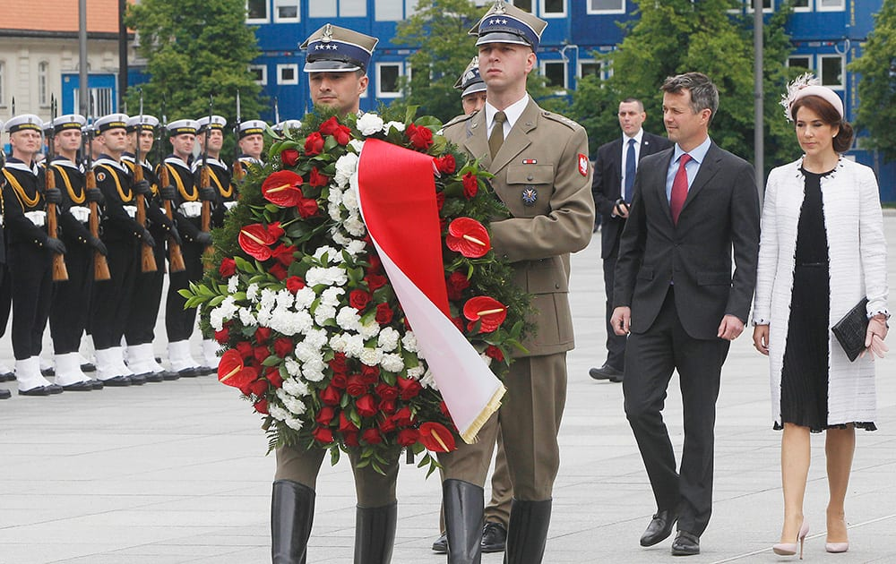 Denmark`s Crown Prince Frederik and Crown Princess Mary follow soldiers during the wreath laying ceremony at the Tomb of the Unknown Soldier in Warsaw, Poland.