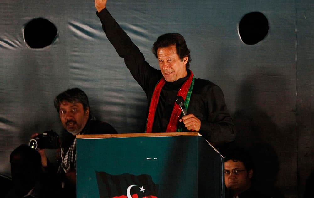 Imran Khan, head of Pakistan Tehreek-e-Insaf or Movement for Justice, raises his arm for his supporters during a rally in Islamabad.
