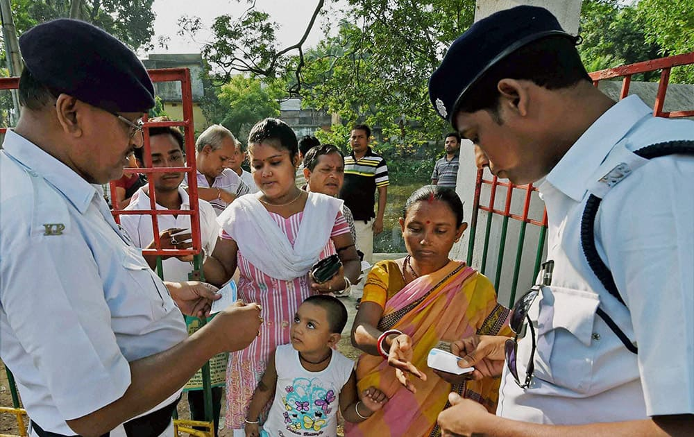 Policemen checking identity cards of voters outside a polling booth during the last phase of Lok Sabha polls in Kolkata.
