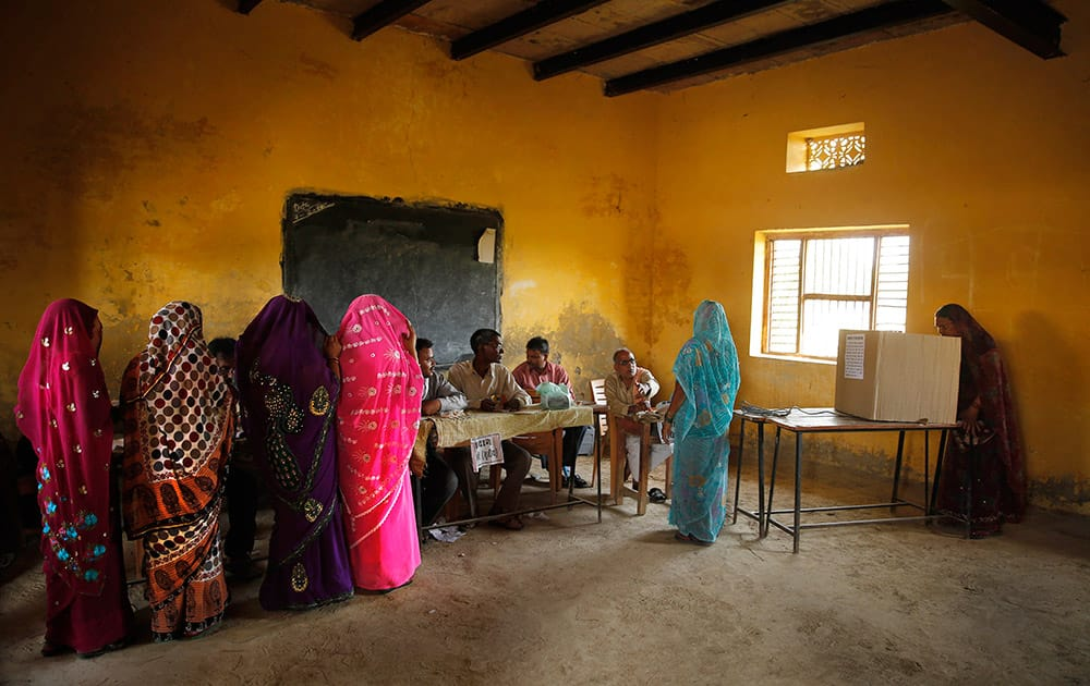 Rural Hindu women with their faces covered wait in a queue as another woman casts her vote on the final day of polling in Kunwarpur village, about 40 kilometers (25 miles) northwest of Jaunpur district, in the northern Indian state of Uttar Pradesh.