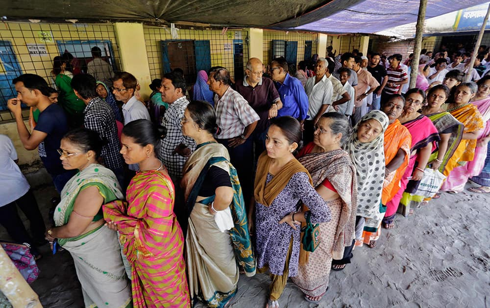 People stand in a queue to cast their vote at a polling station in Kamalgaji, on the outskirts of Kolkata.