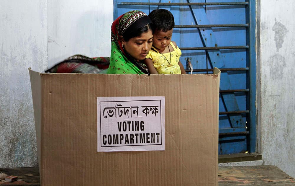 A woman carries her child while casting her vote on the final day of polling in Kamalgaji, on the outskirts of Kolkata.
