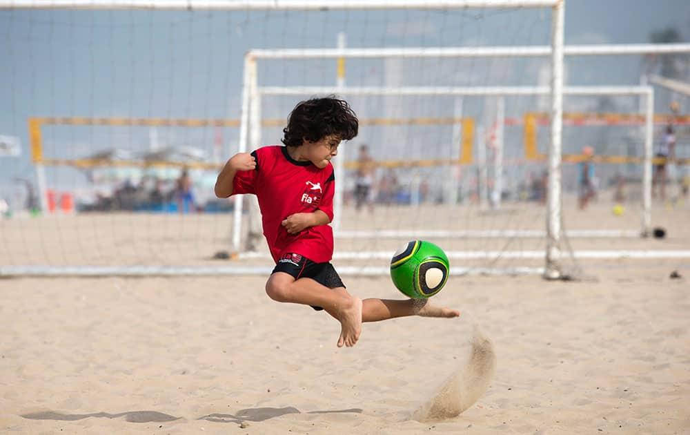 A boy controls the ball as he trains on Ipanema beach in Rio de Janeiro, Brazil.