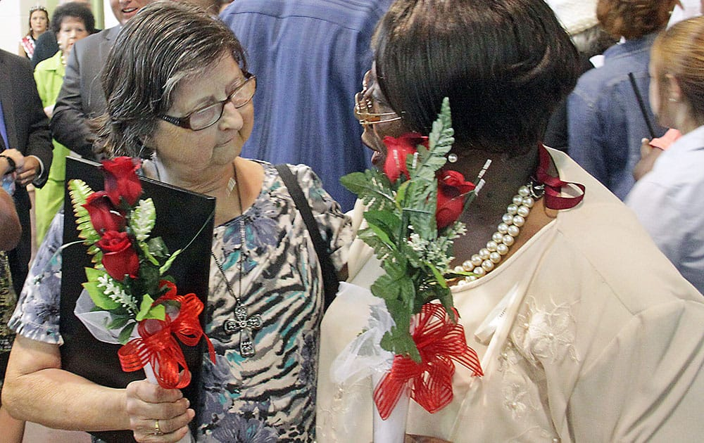 Connie Buggs, left, and Nancy Dupree, who both lost family members in the April 28, 2014, tornado attend a community memorial service for the 10 Winston County residents killed in Louisville, Miss.