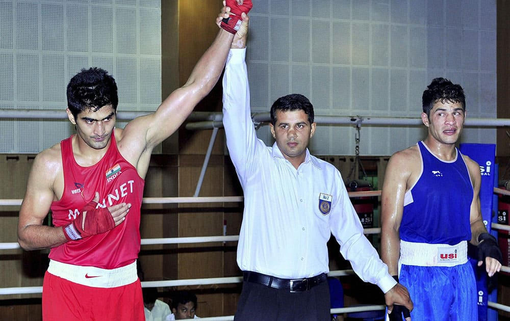 Boxer Vijender Singh is declared winner after a fight during selection trials for the core group probables for Commonwealth Games and Asian Games 2014, in Patiala.