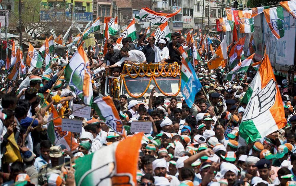 Congress Vice President Rahul Gandhi shakes hands with supporters during a road show for party candidate Ajay Rai in Varanasi.