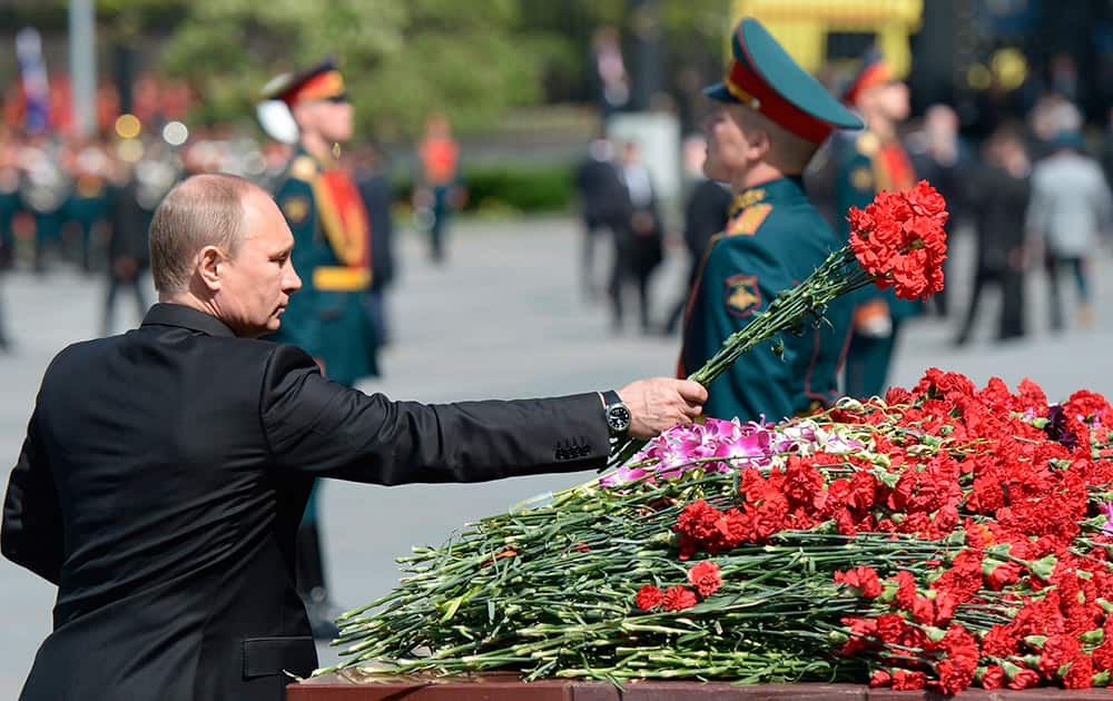 Russian President Vladimir Putin lays flowers during a wreath laying ceremony at the Tomb of Unknown Soldier, at the Kremlin wall on the eve of Victory Day in Moscow, Russia.
