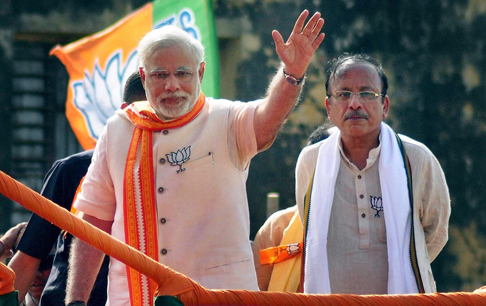 BJP PM candidate Narendra Modi waves during an election road show in Varanasi.