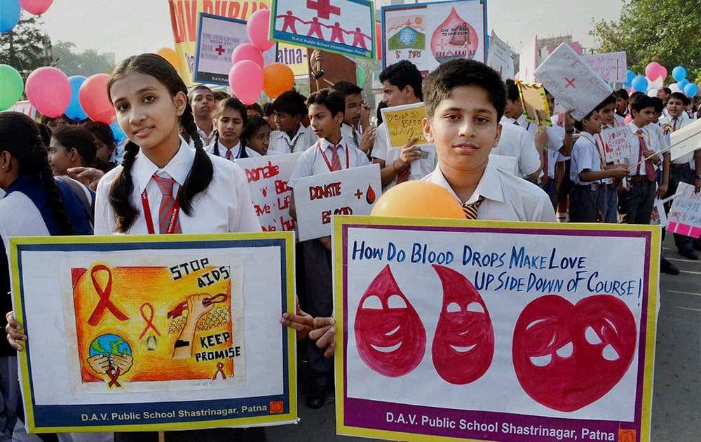 School students carry placards during an awarness rally on World Red Cross Day in Patna.