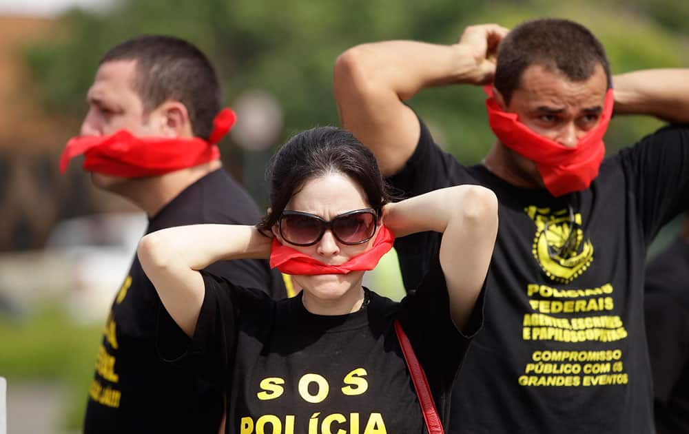 Federal police wearing T-shirts that read in Portuguese `SOS Federal Police` cover their mouths with bandanas as a way to protest their leaders` recommendation to not protest, as they demand better labor conditions outside the venue where Brazil`s coach is announcing his squad for the upcoming World Cup in Rio de Janeiro, Brazil.