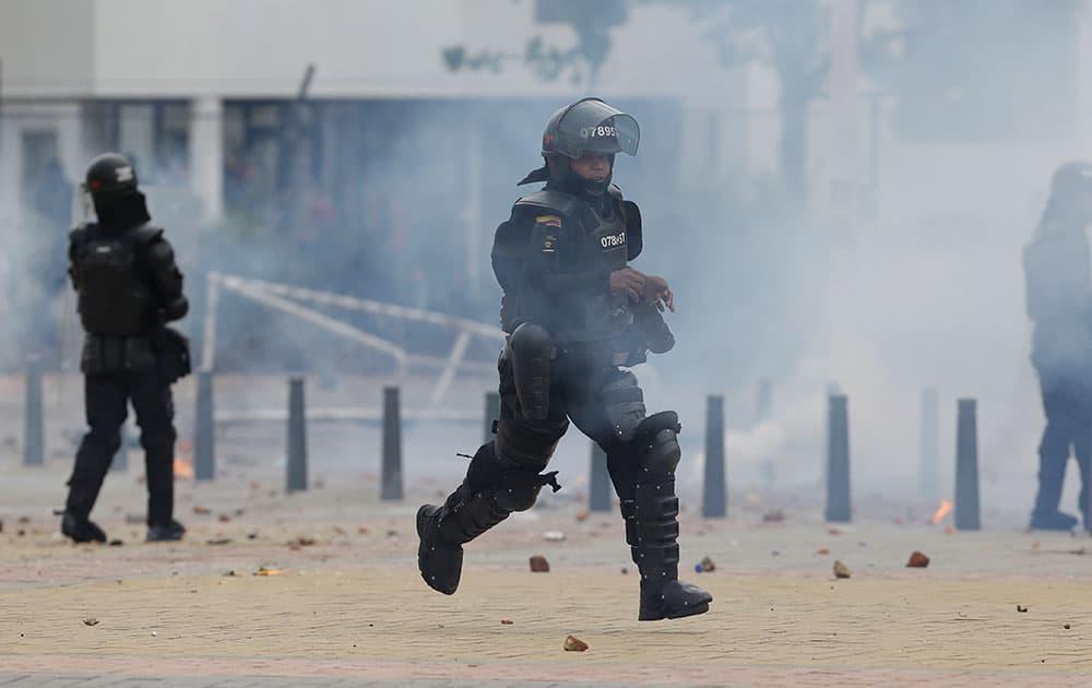 A riot police officer runs to get more tear gas during confrontations with students who gathered outside the Universidad Nacional in Bogota, to show their support for the ongoing nationwide agrarian strikes, in Bogota, Colombia.