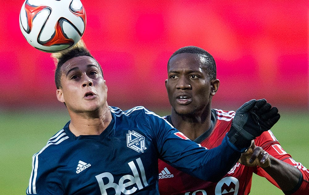 Toronto FC defender Doneil Henry, right, battles for the ball against Vancouver Whitecaps forward Erik Hurtado, left, during first half semi-final Amway Canadian Championship soccer action in Toronto.