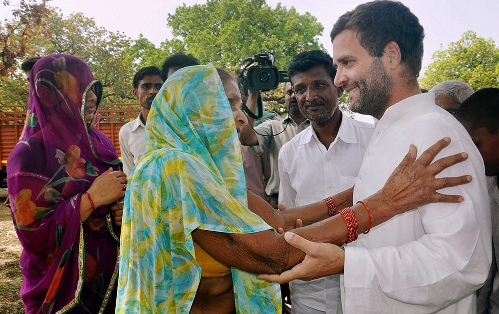 An elderly woman interacts with Rahul Gandhi outside a polling station in Amethi, Uttar Pradesh.