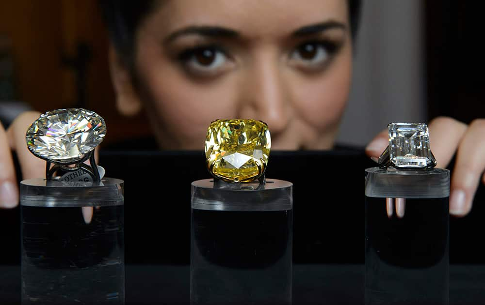 A Sotheby`s employee shows three exceptional diamonds during a preview at the Sotheby`s, in Geneva, Switzerland.