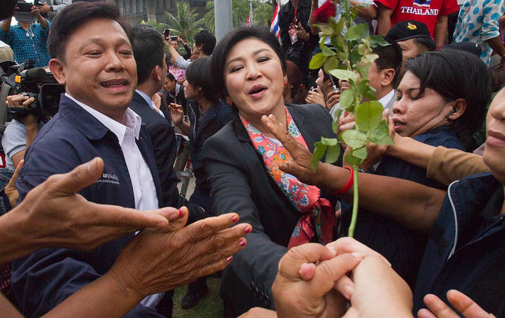 Thai Prime Minister Yingluck Shinawatra shakes hand with her supporters in Bangkok.