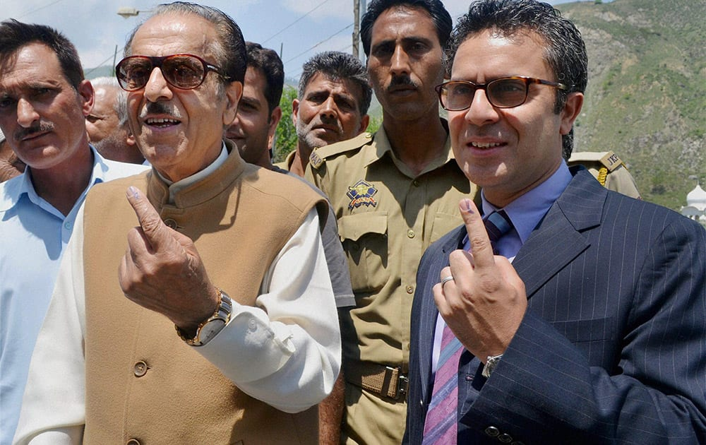 Jammu and Kashmir Pradesh Congress Committee (JKPCC) chief Saifuddin Soz and his son Salman Soz show their inked fingers after casting votes for Lok Sabha polls at a polling station at Khanpora in Baramulla.