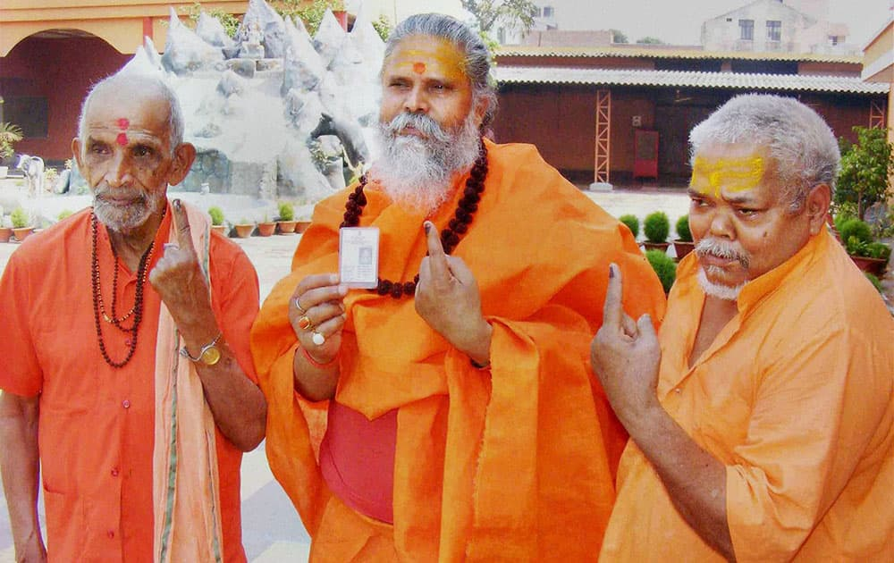 Mahant Narendra Giri Ji Maharaj and other sadhus show their inked fingers in Allahabad.