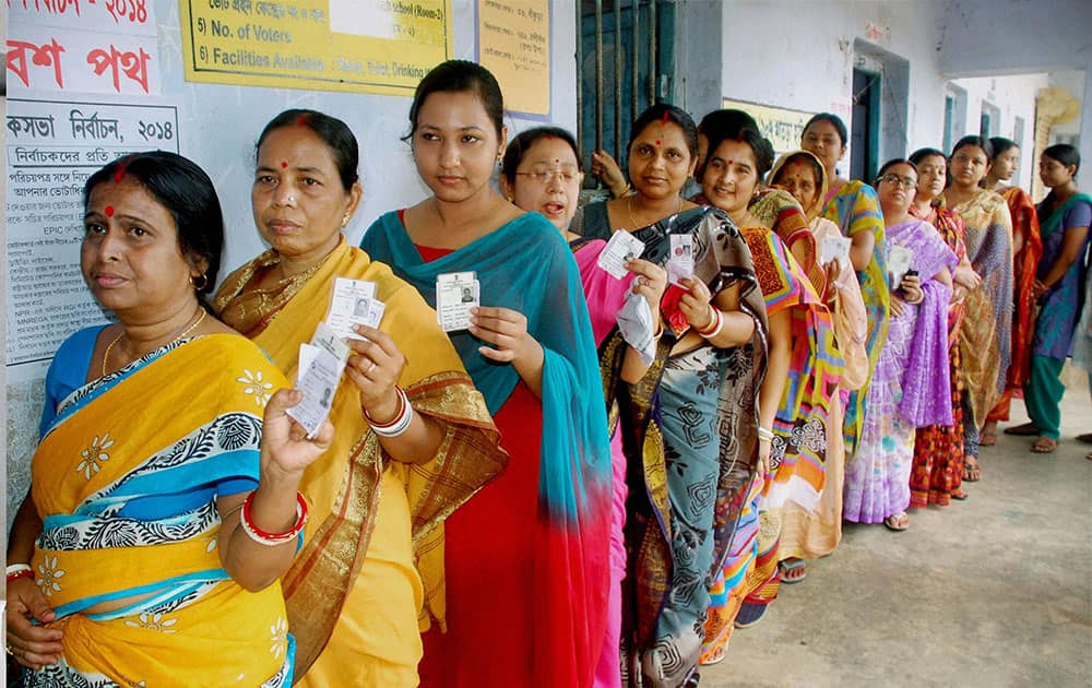 Women voters showing their voter identity cards as they wait in a queue to cast their vote at a polling booth at Bankura district in West Bengal.