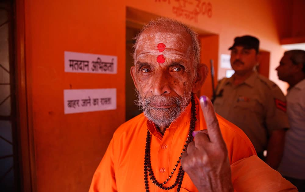 A Hindu holy man displays the indelible ink mark on his finger as he returns after casting his vote during the eighth phase of voting of the Indian parliamentary elections in Allahabad.