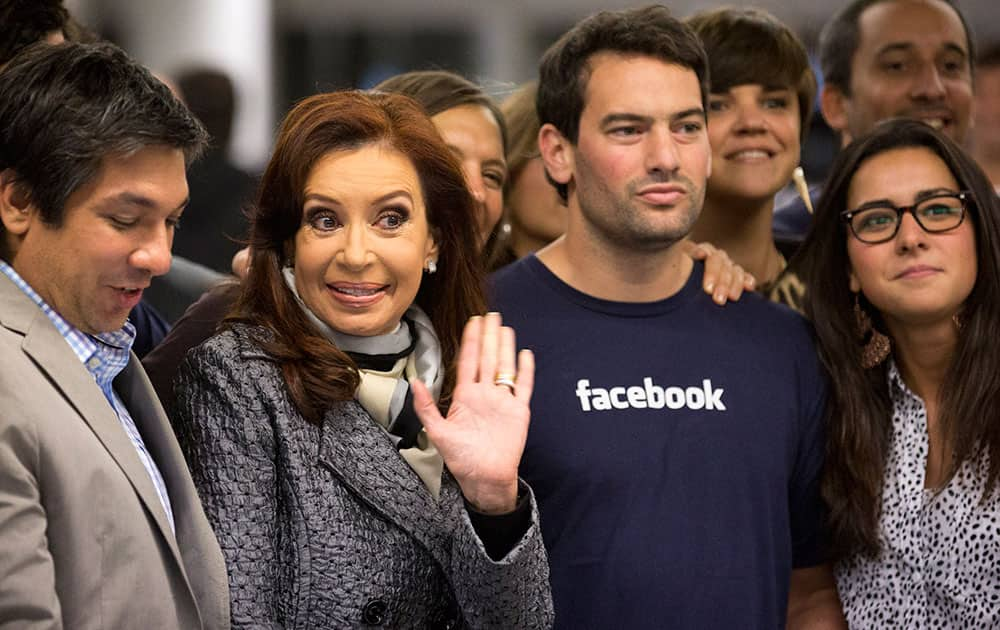 Argentine President Cristina Fernandez waves to photographers as she meets employees during a tour of the new Facebook offices` in Buenos Aires, Argentina.
