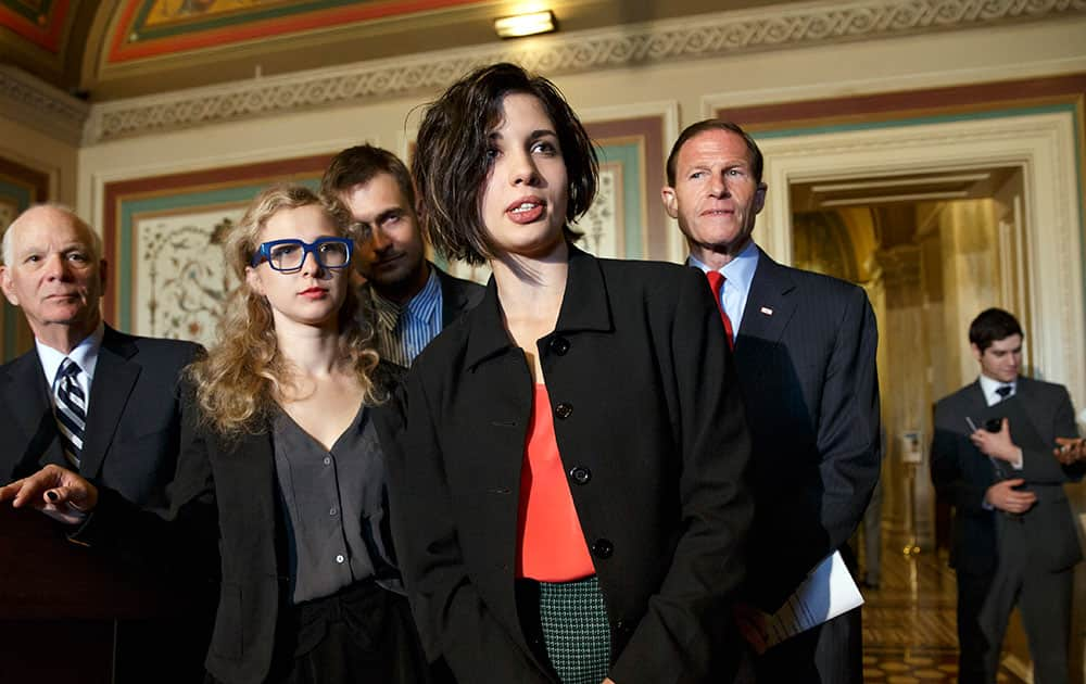 Russian political activists Nadya Tolokonnikova, center, and Maria Alyokhina, center left, of the Russian punk rock protest group Pussy Riot, join Sen. Richard Blumenthal, D-Conn., right, and Sen. Ben Cardin, D-Md., far left, the chairman of the Helsinki Commission, in seeking action to stop violations of human rights by pro-Russian militants in the Ukraine region, at the Capitol in Washington.