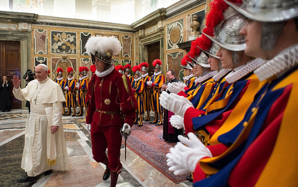 Pope Francis, flanked by Swiss Guards Commander Daniel Rudolf Anrig, greets new Swiss Guards the day before their swearing-in ceremony, as he arrives to meet them in the Clementine hall at the Vatican.