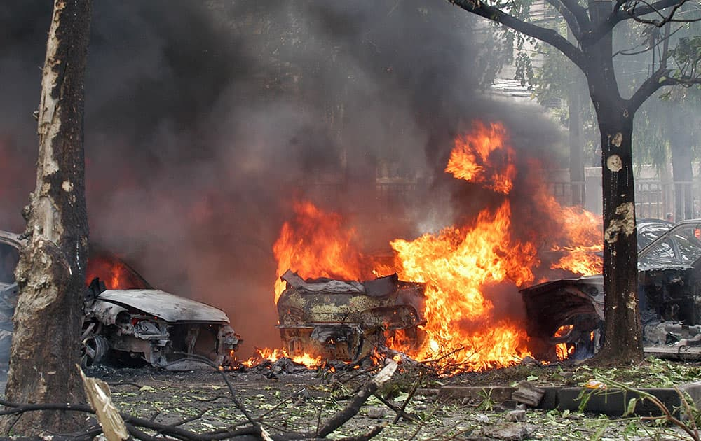 Cars are engulfed in flames after a bomb hidden in a car exploded at a police station parking lot in Hat Yai district in Songkhla province, southern Thailand.