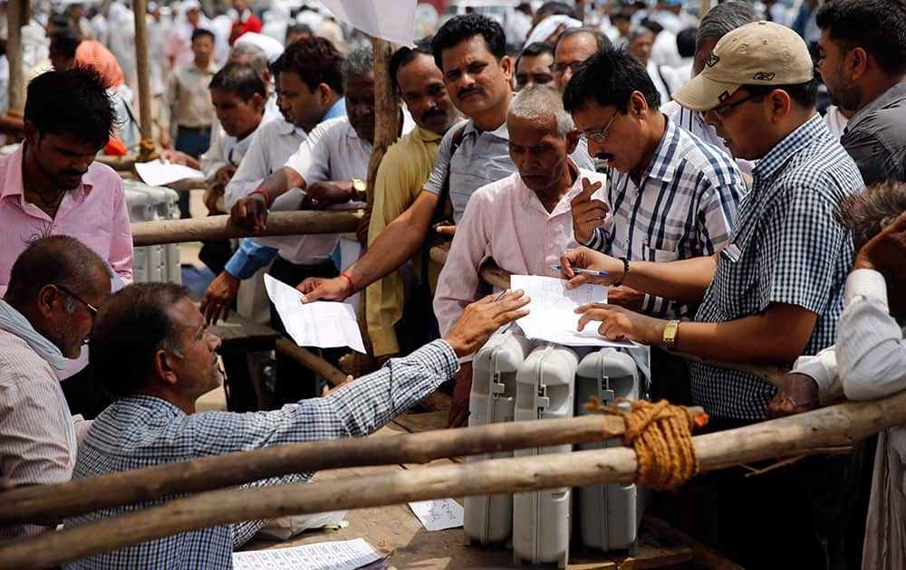 Election officers crowd around a distribution center to receive electronic voting machines for their respective polling stations on the eve of polling in Allahabad, in the northern Indian state of Uttar Pradesh.