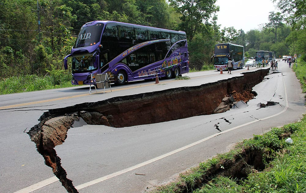 Buses carrying tourists slowly cruise through a cracked road after an earthquake in Chiang Rai province, northern Thailand. Officials said Tuesday that one person was killed and several dozen were hurt in an earthquake that struck northern Thailand and Myanmar a day earlier, smashing windows, cracking walls and roads and damaging Buddhist temples.