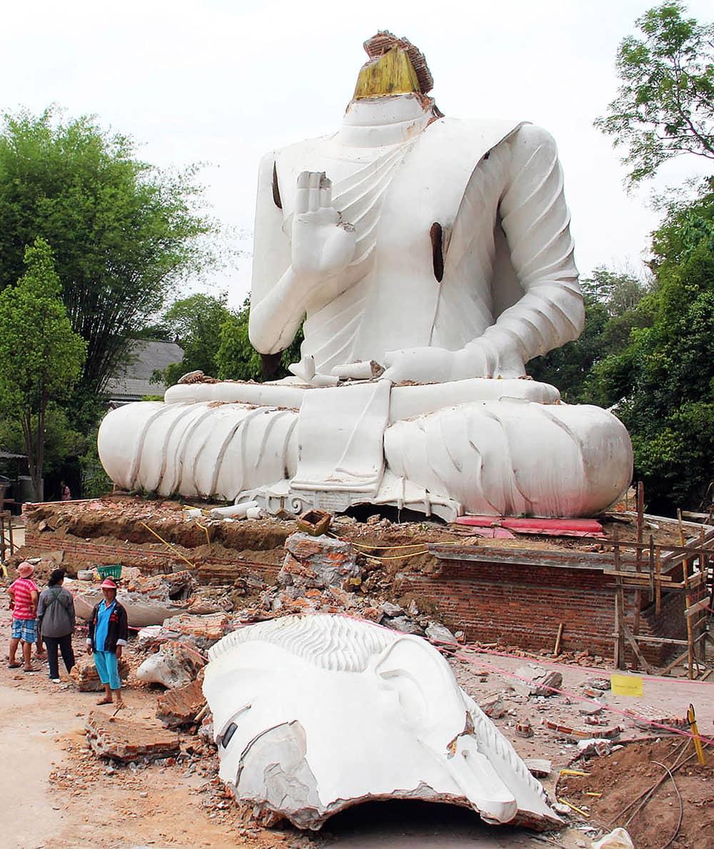 Thai villagers examine a damaged Buddha statue following an earthquake in Chiang Rai province, northern Thailand.