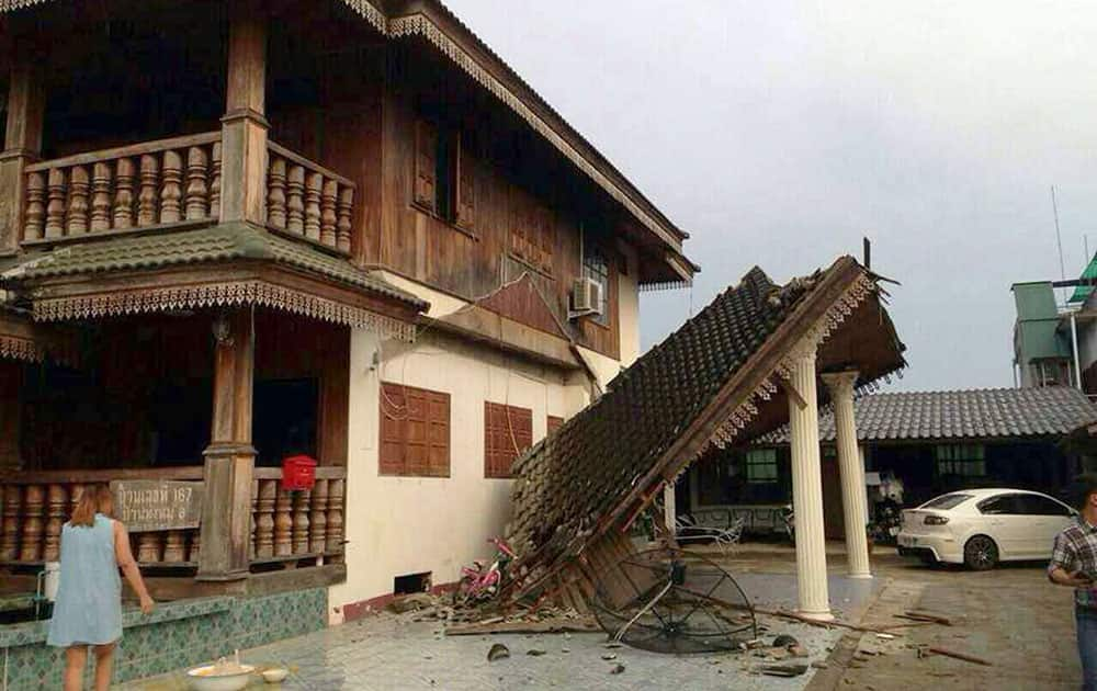 A woman looks at a partly damaged house following an earthquake in Chiang Rai province, northern Thailand.