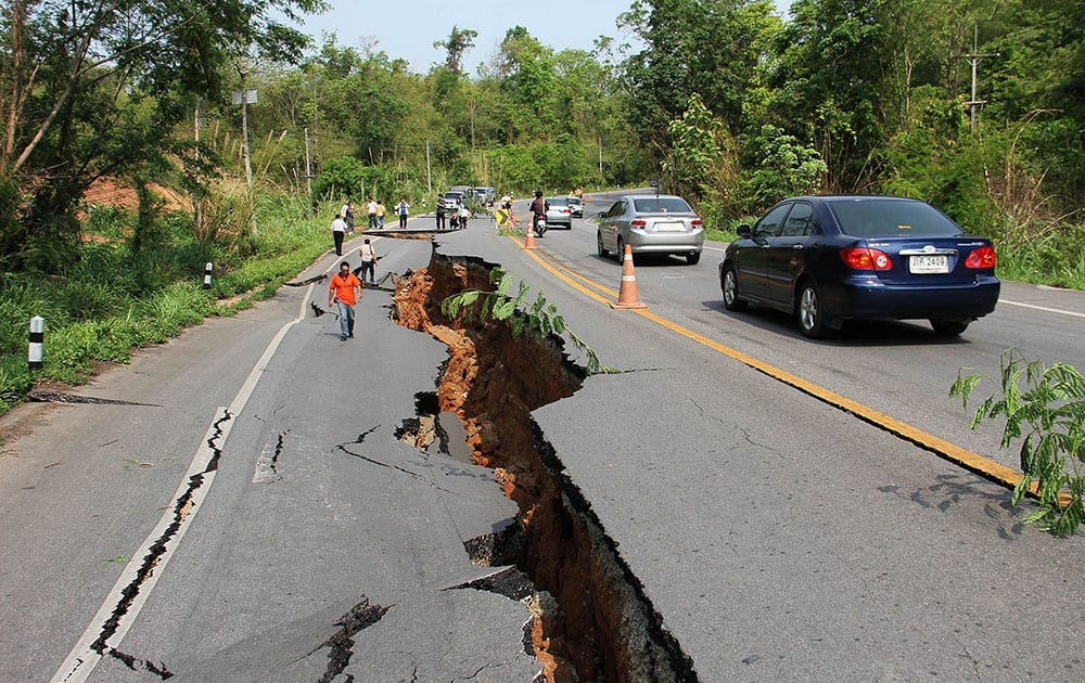 Motorists make their way through as people examine a cracked road after an earthquake in Chiang Rai province, northern Thailand.