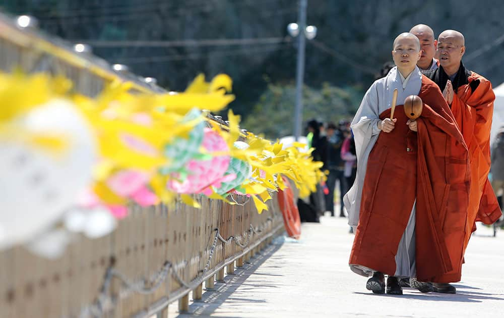 Monks march during a Buddhist ceremony for cherishing the memory of the deceased and the missing passengers of the sunken ferry Sewol, at a port in Jindo, south of Seoul, South Korea.