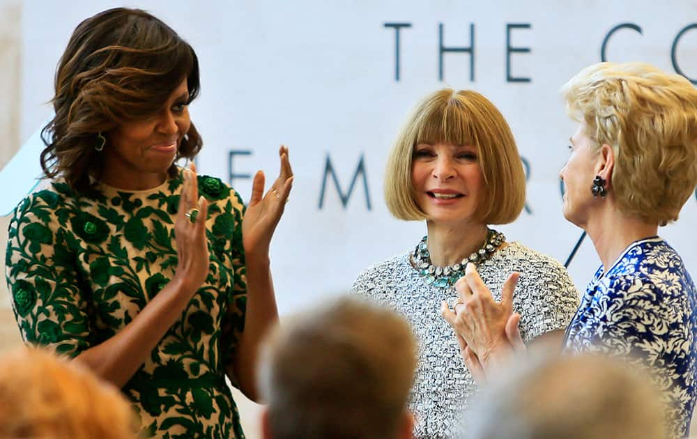 First lady Michelle Obama, left, and Metropolitan Museum of Art president Emily Rafferty, right, applaud Vogue editor Anna Wintour at a dedication ceremony for the Anna Wintour Costume Center, at the Metropolitan Museum of Art in New York.