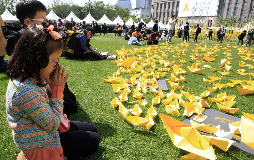 A girl prays in front of paper ships bearing messages for the victims of the sunken ferry Sewol at a group memorial altar in Seoul, South Korea.