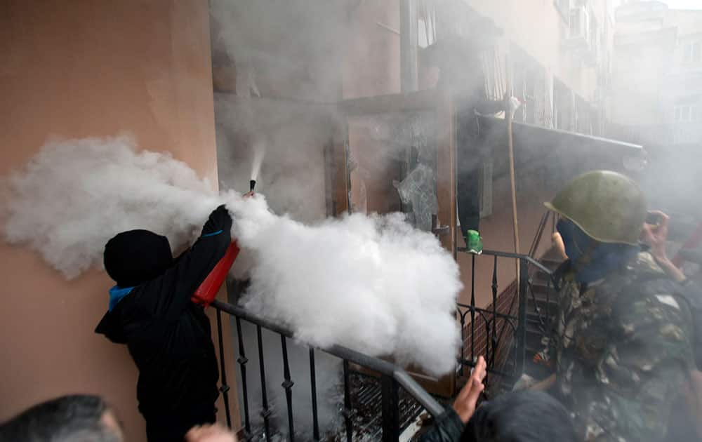 A pro-Russian protester fires a fire extinguisher at riot police inside at a police station building in Odessa, Ukraine.