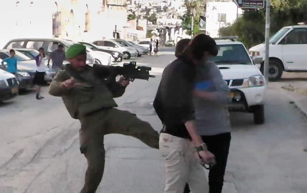 In this image taken from video obtained from Youth Against Settlements, a group of Palestinian activists, which has been authenticated based on its contents and other AP reporting, an Israeli soldier kicks at Palestinian teens in the West Bank city of Hebron.